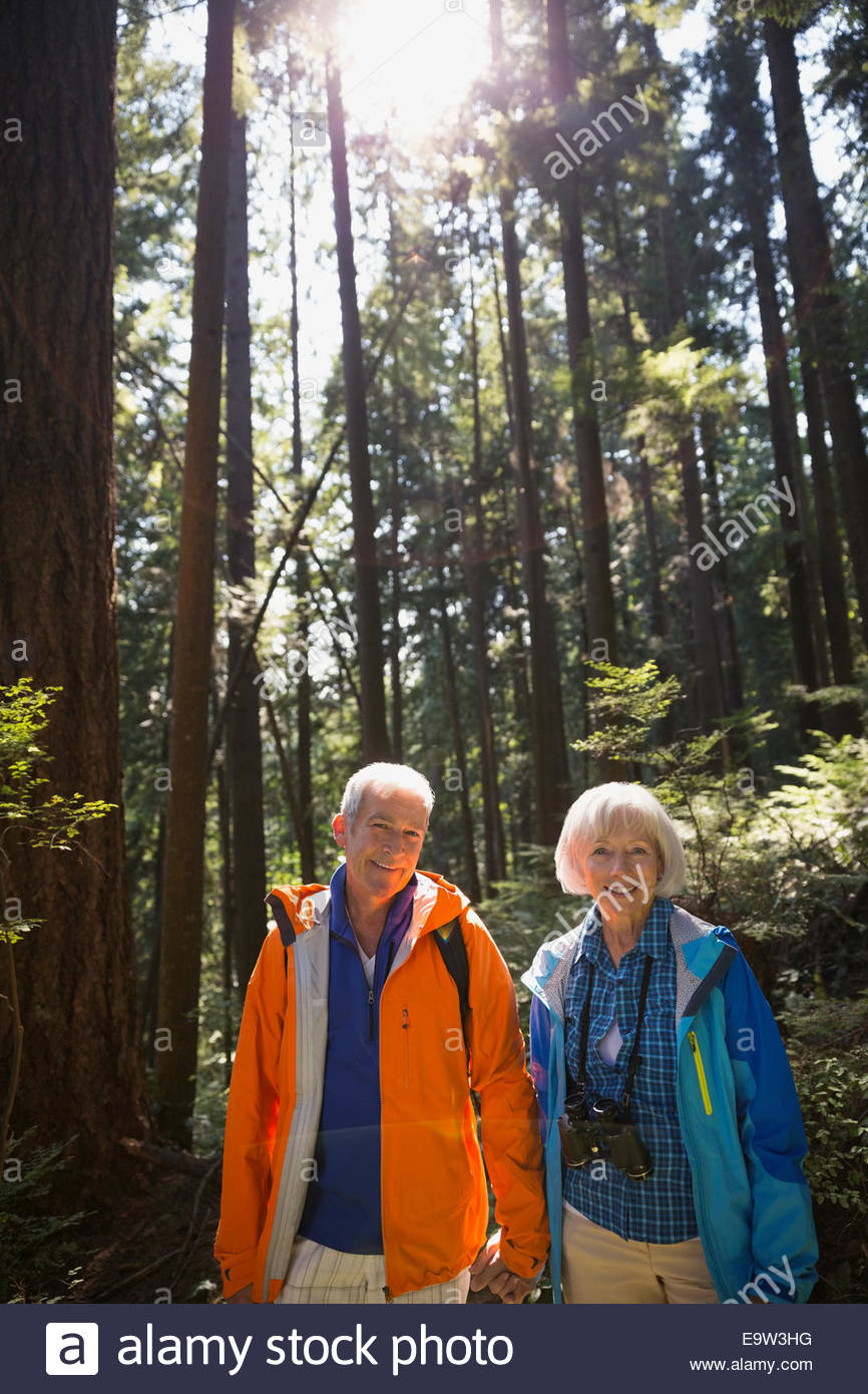 Portrait of smiling senior couple in sunny woods - Stock Image