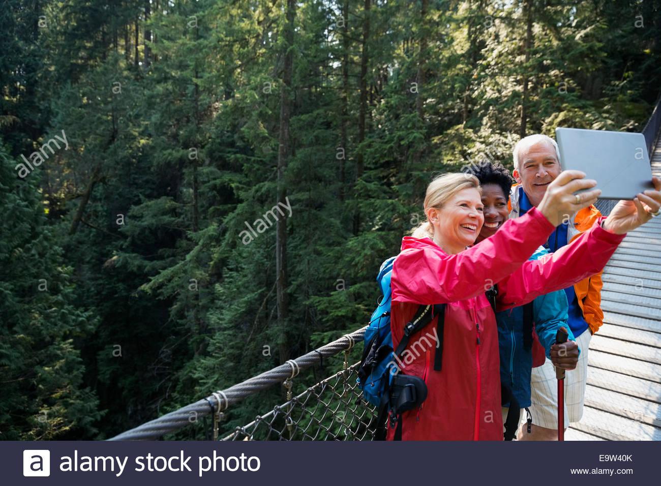 Friends taking selfie with digital tablet on footbridge - Stock Image