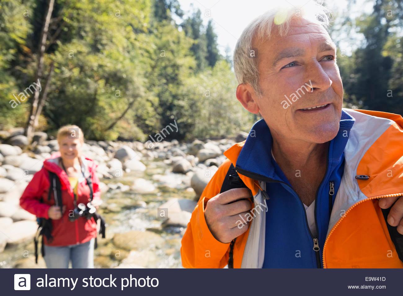 Senior man hiking in sunny woods - Stock Image