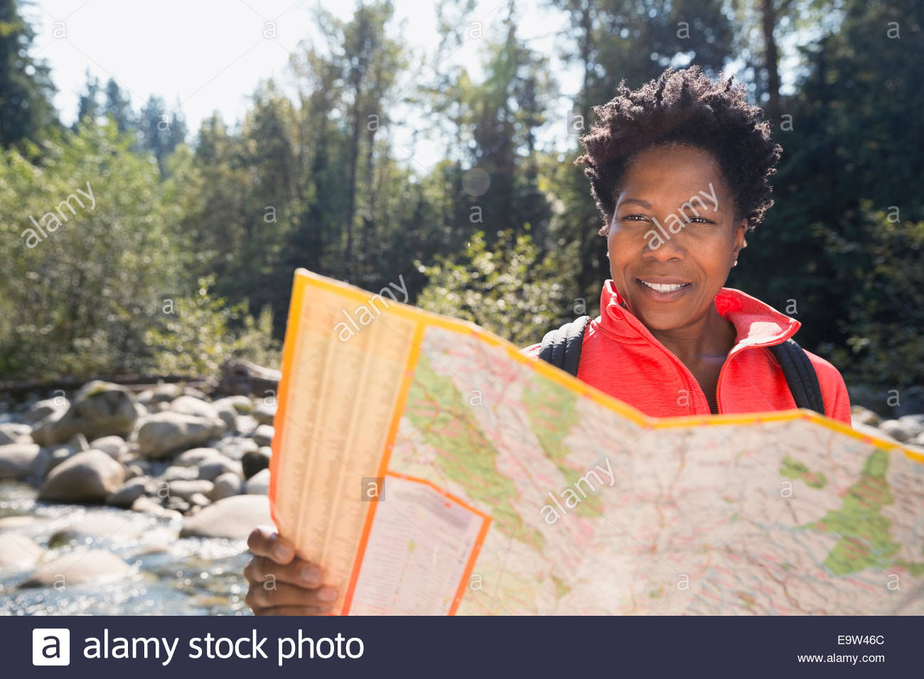 Woman looking at trail map in sunny woods - Stock Image