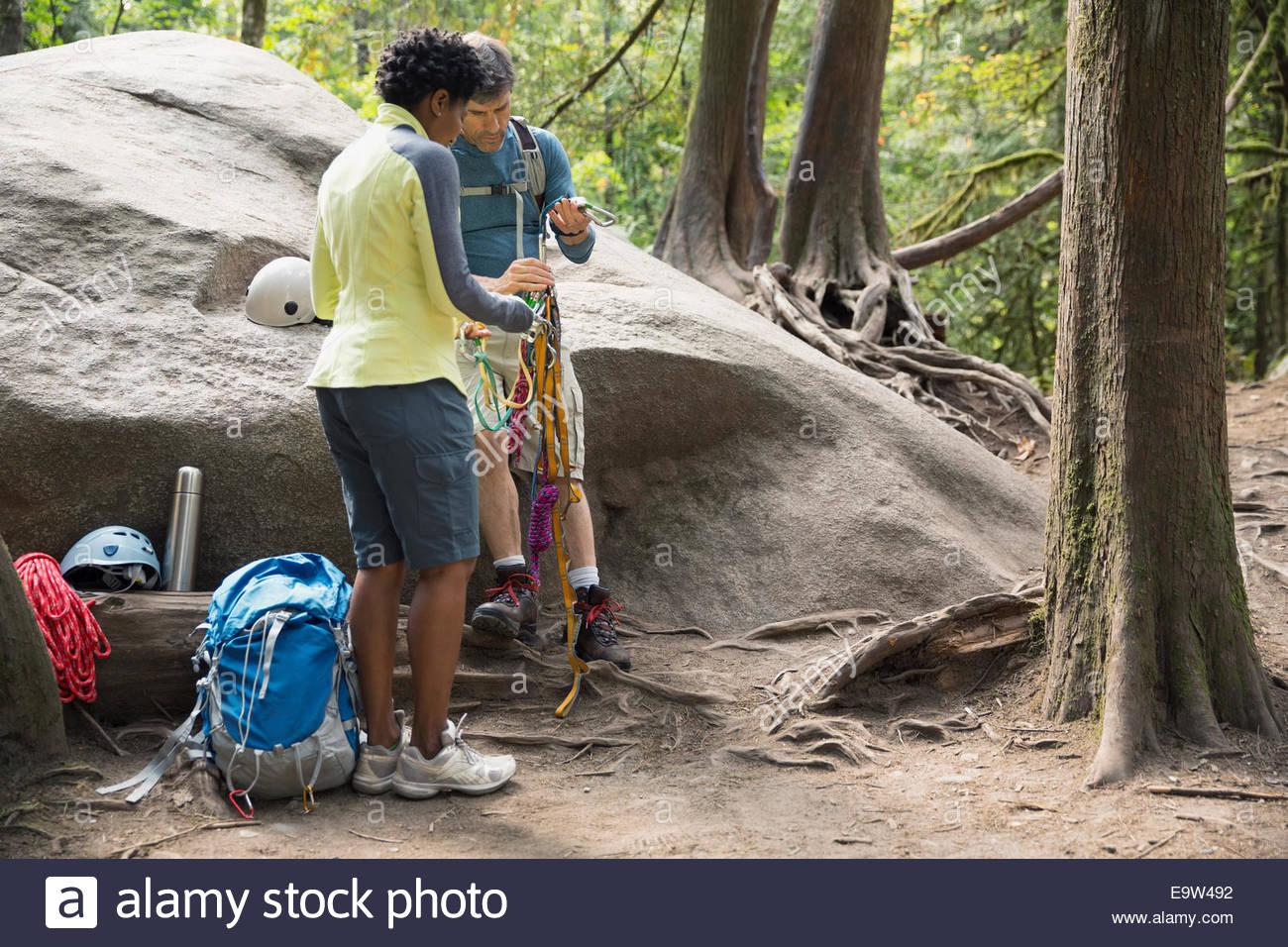 Couple organizing rock climbing equipment in woods - Stock Image