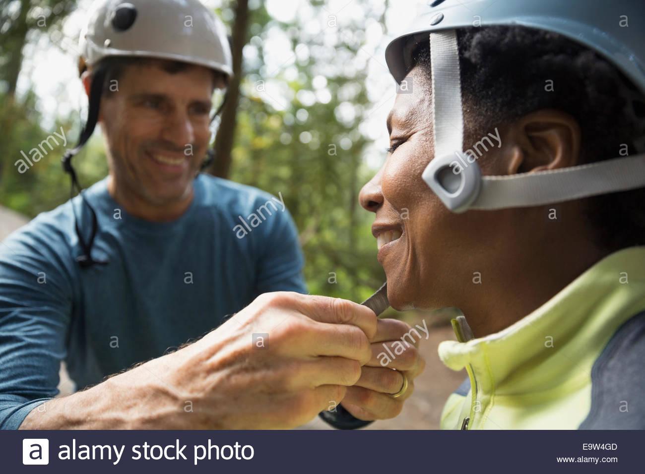 Man fastening womans rock climbing helmet - Stock Image