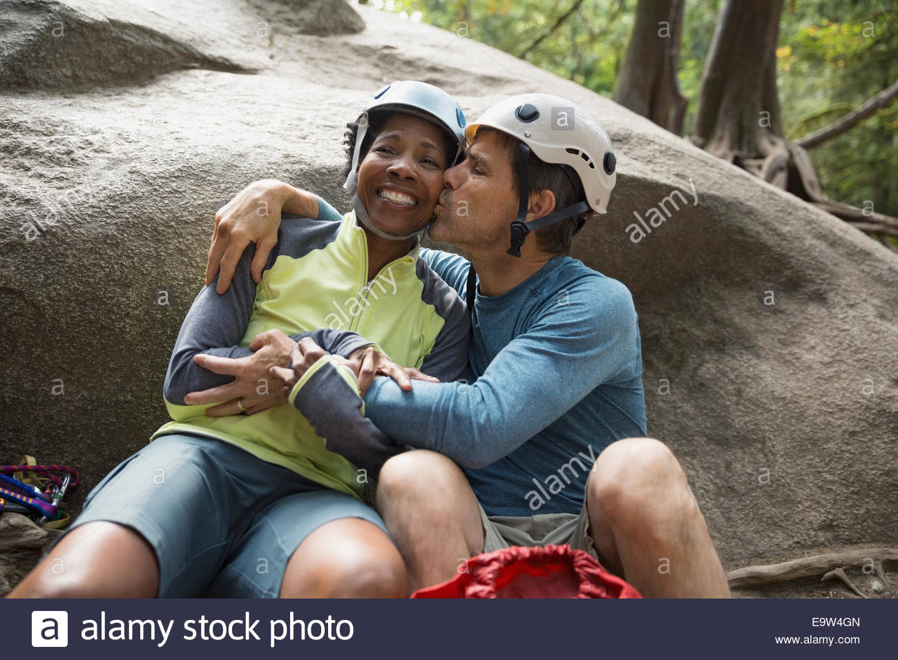 Couple in rock climbing helmets kissing against rock - Stock Image