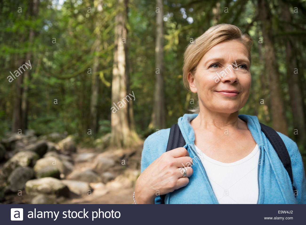 Smiling woman hiking in woods - Stock Image