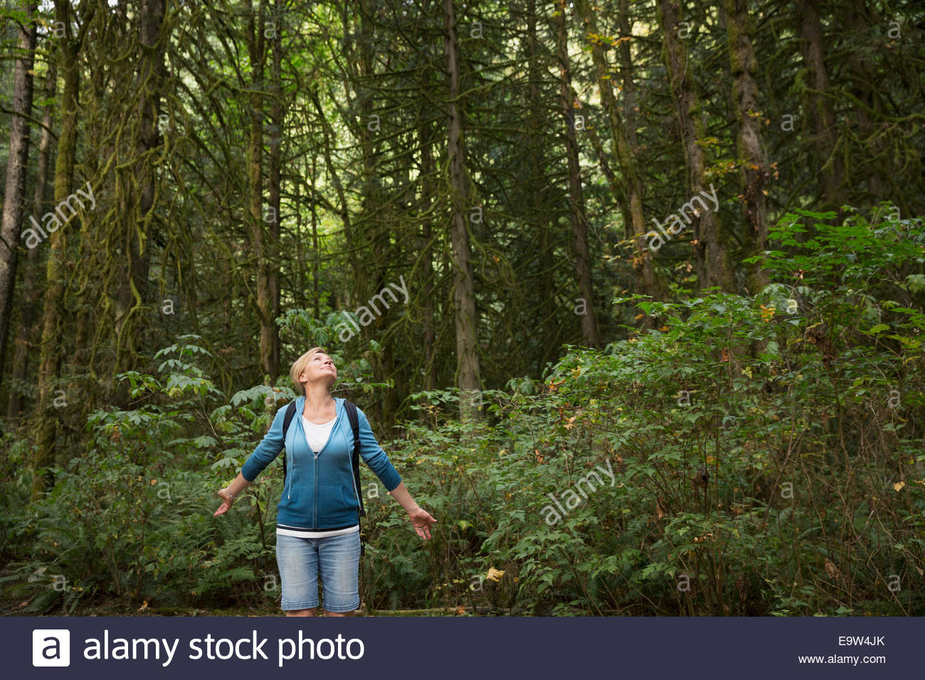 Woman with arms outstretched in woods - Stock Image