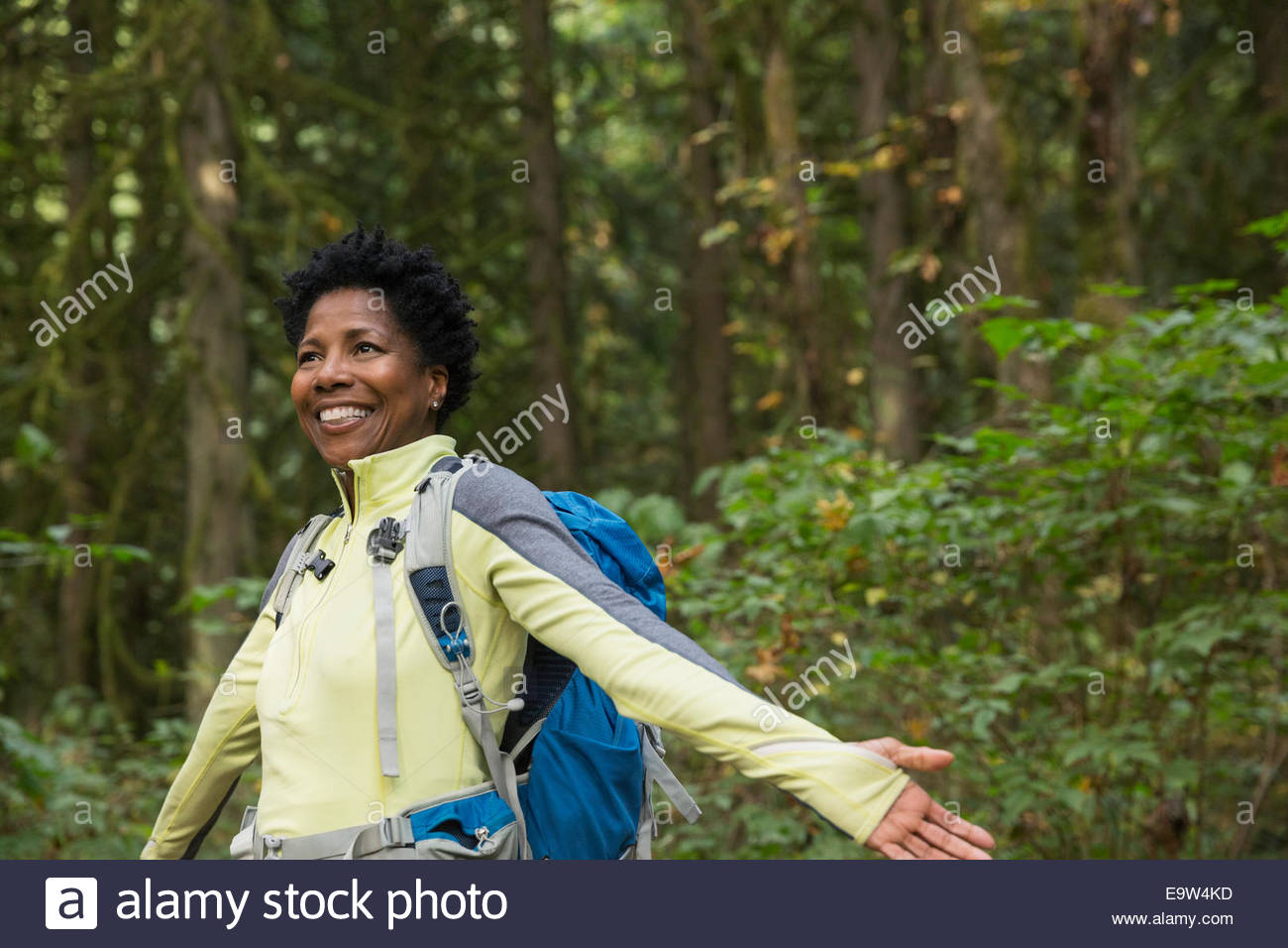 Smiling woman with arms outstretched in woods - Stock Image