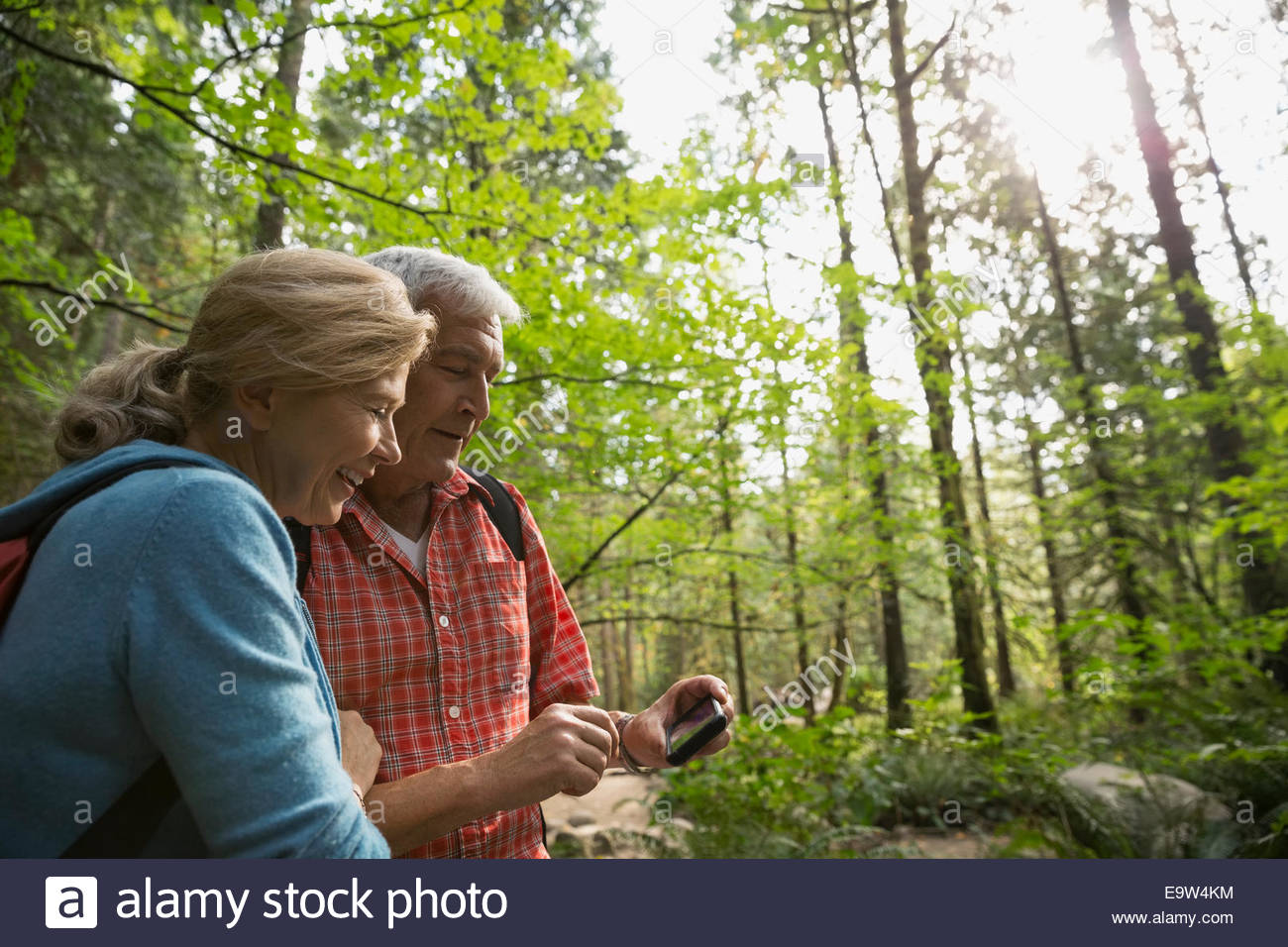 Couple looking at camera phone in woods - Stock Image
