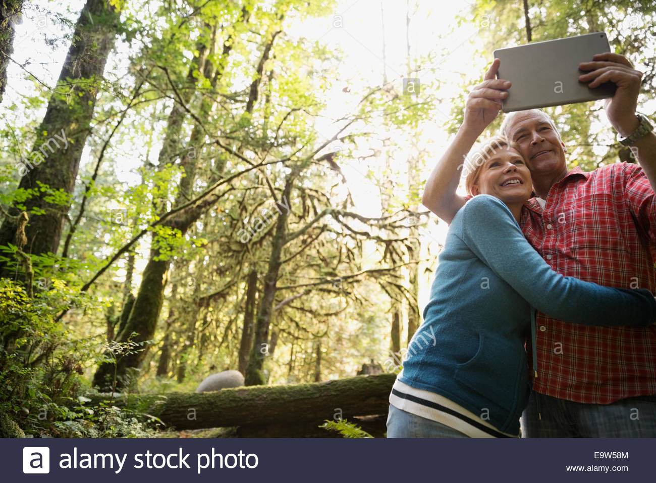 Couple taking selfie with digital tablet in woods Stock Photo
