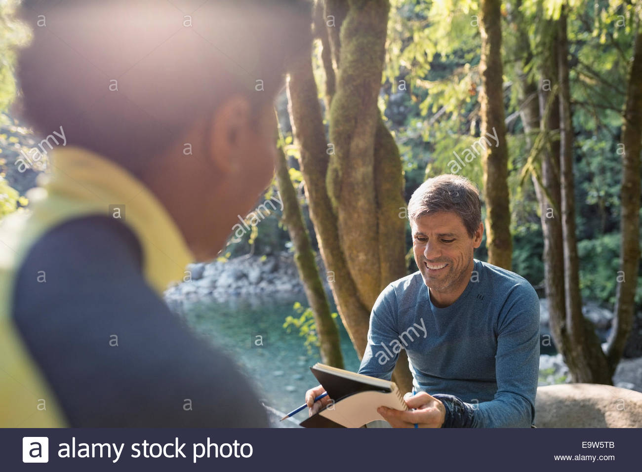 Couple with notebook at creekside in woods - Stock Image