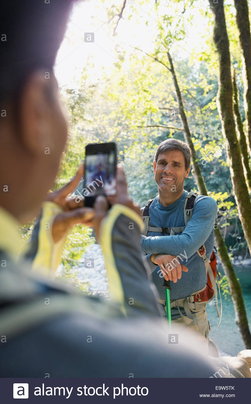 Woman photographing man in sunny woods - Stock Image