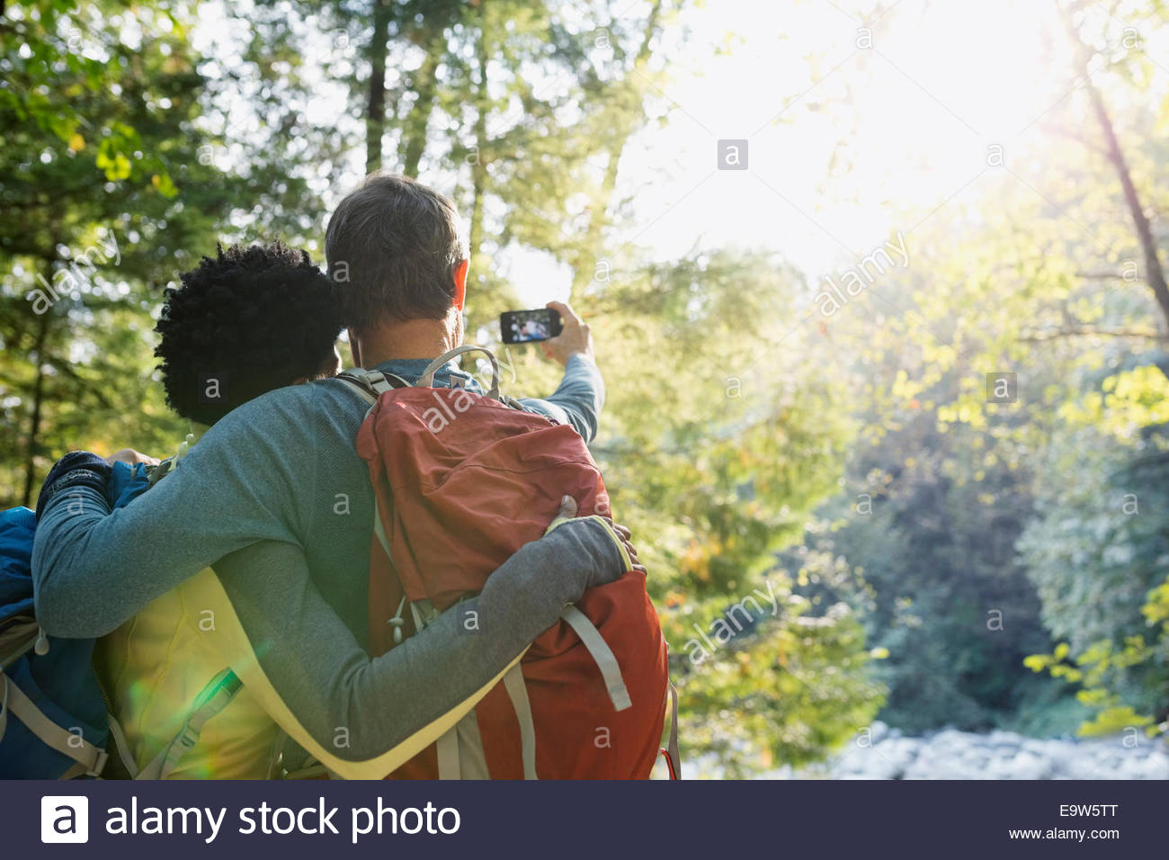 Couple taking selfie in sunny woods - Stock Image