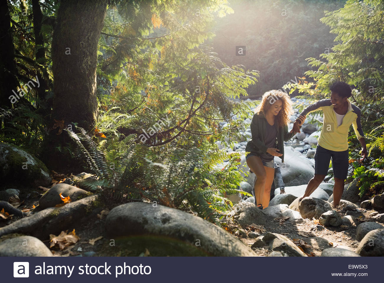 Mother and daughter hiking in sunny woods - Stock Image