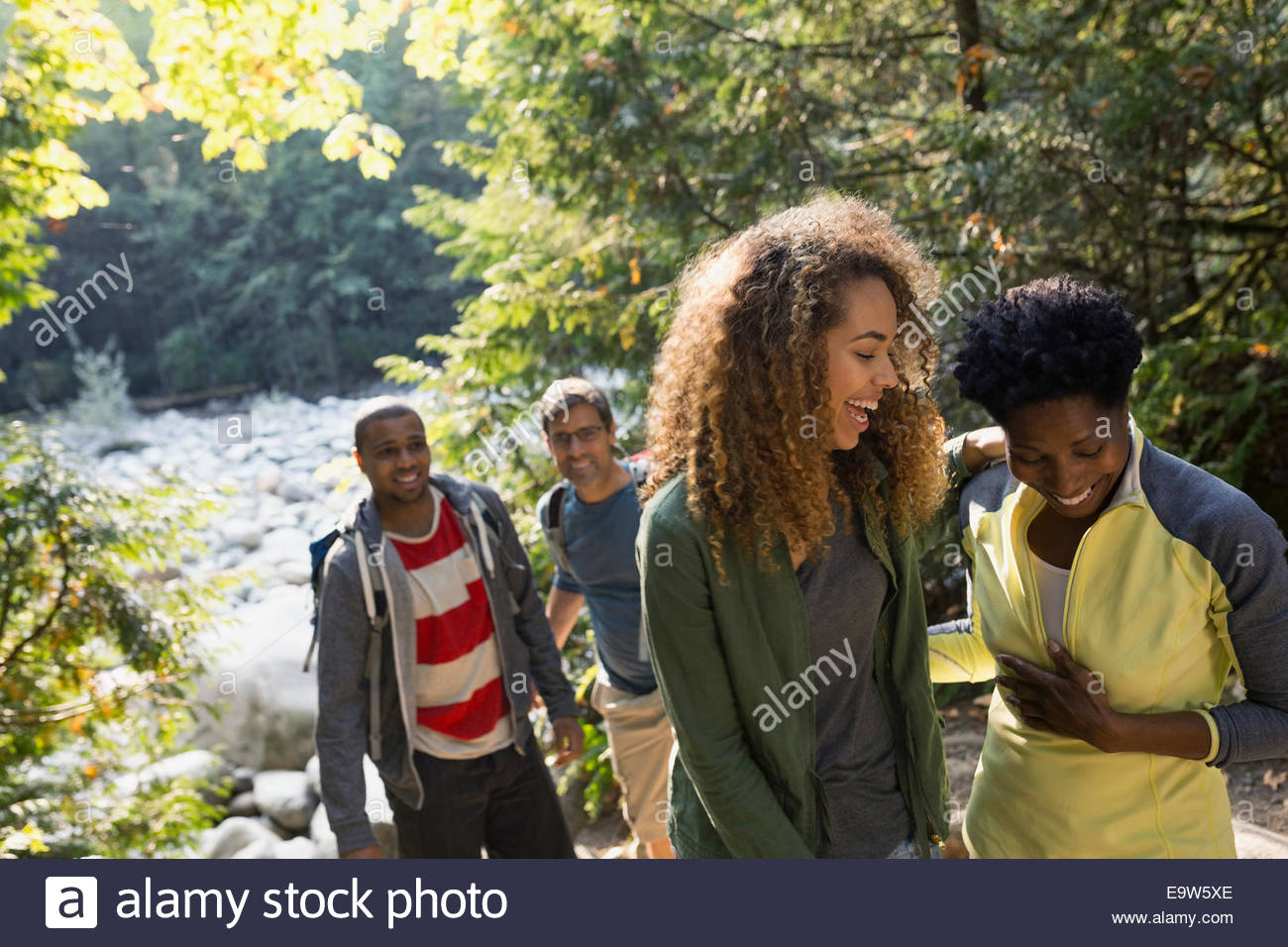 Friends laughing in sunny woods - Stock Image