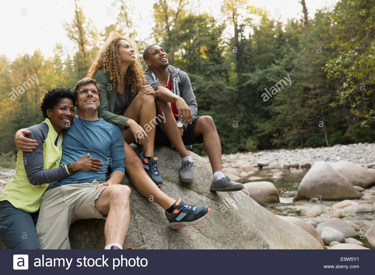 Friends on large rock in woods - Stock Image