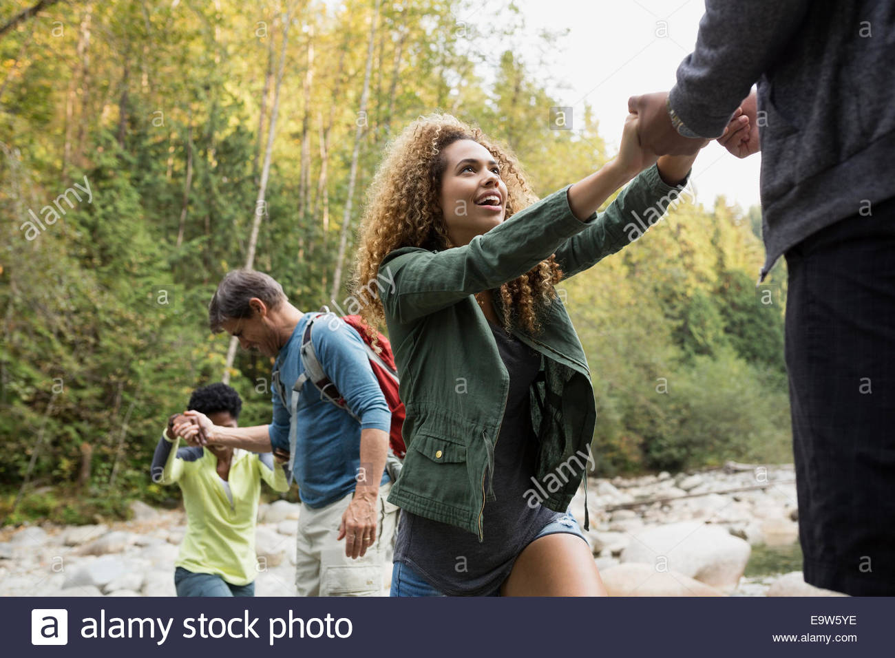 Friends crossing rocks over creek in woods - Stock Image