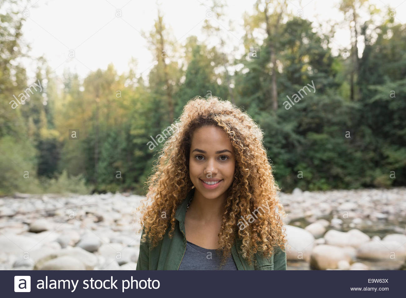 Portrait of smiling woman in woods - Stock Image