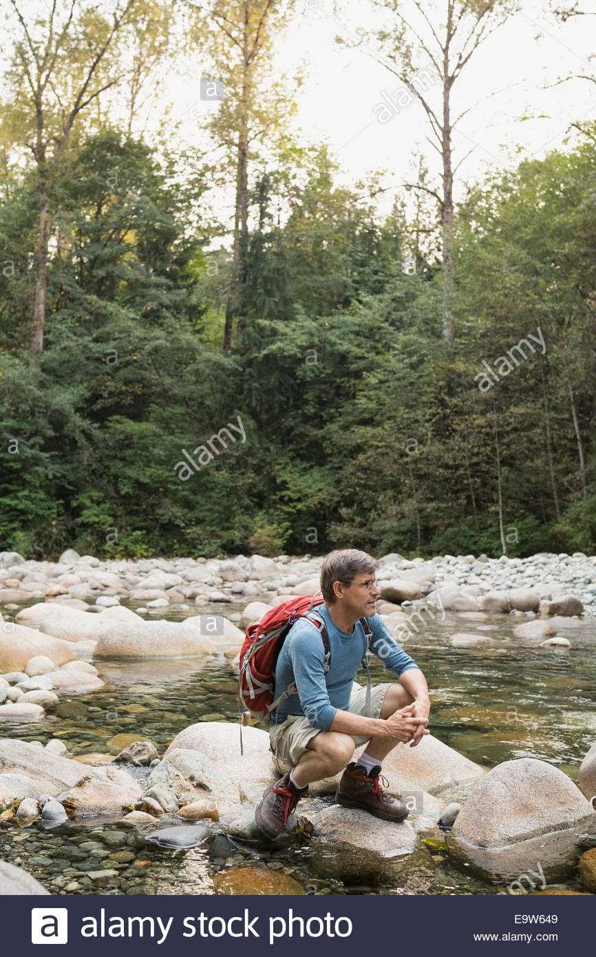 Man with backpack crouching on rock over creek - Stock Image