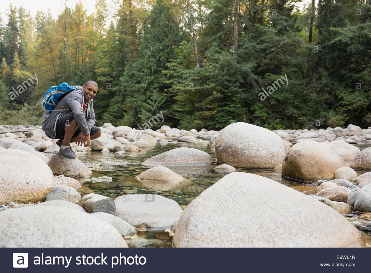 Portrait of man with backpack crouching at creekside - Stock Image