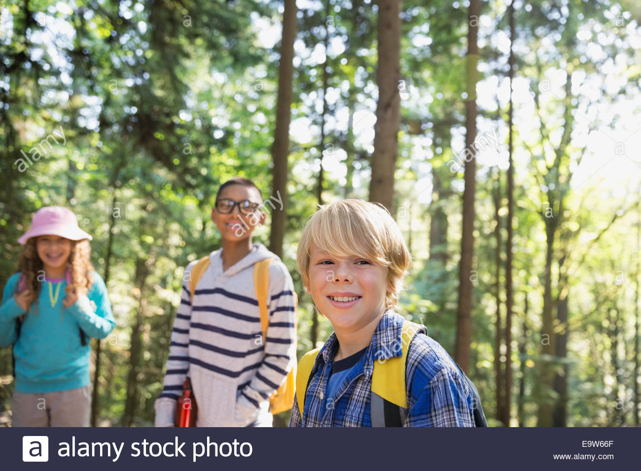 Portrait of smiling boys and girl in woods - Stock Image