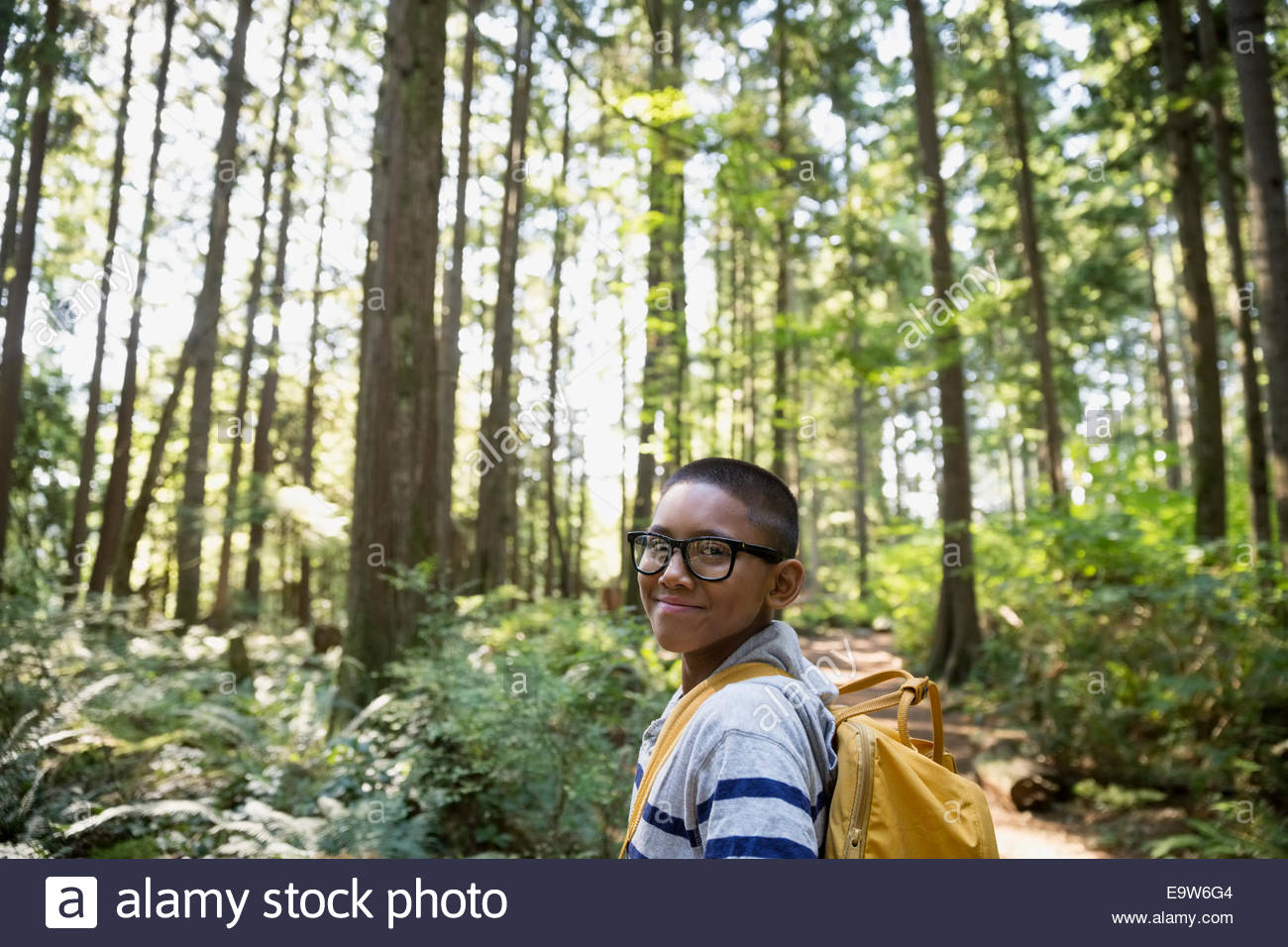 Portrait of smiling boy with backpack in woods - Stock Image