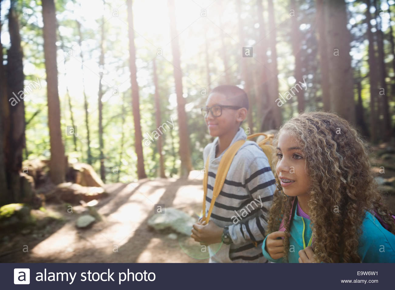 Boy and girl hiking in sunny woods - Stock Image