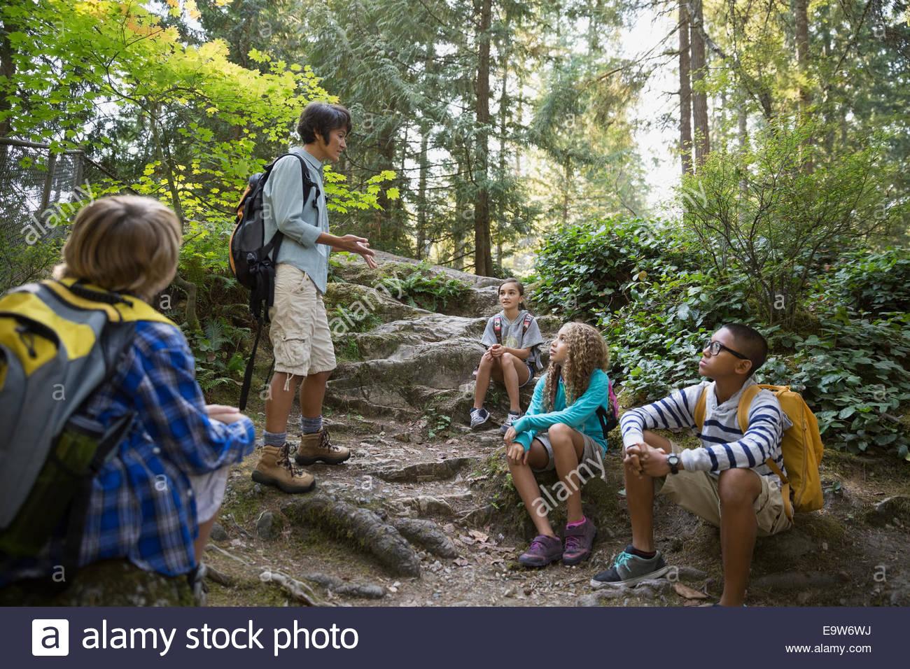 Teacher speaking to children in woods - Stock Image