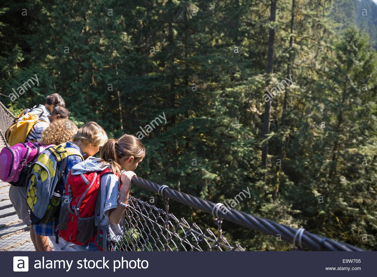 Children with backpacks looking down from footbridge - Stock Image