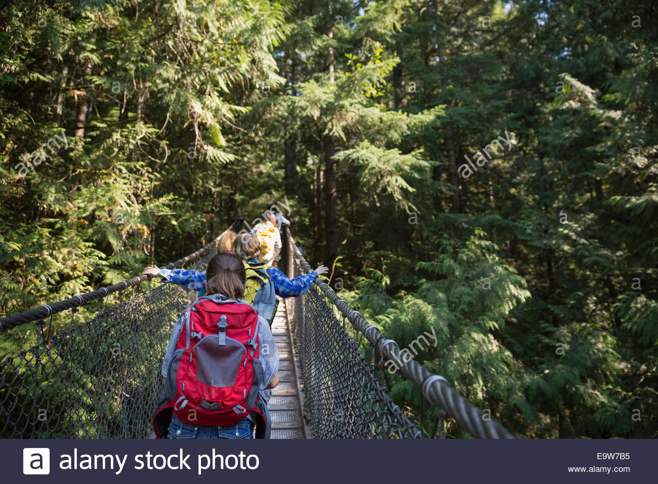 Children with backpacks crossing plank bridge in woods - Stock Image