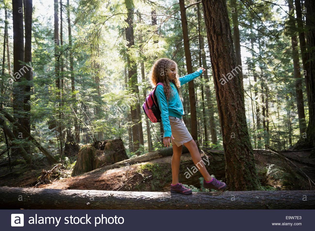 Girl walking on fallen tree in woods - Stock Image