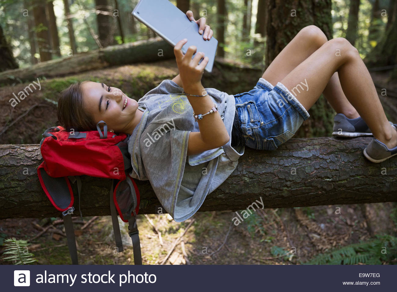 Girl with digital tablet laying on fallen tree - Stock Image