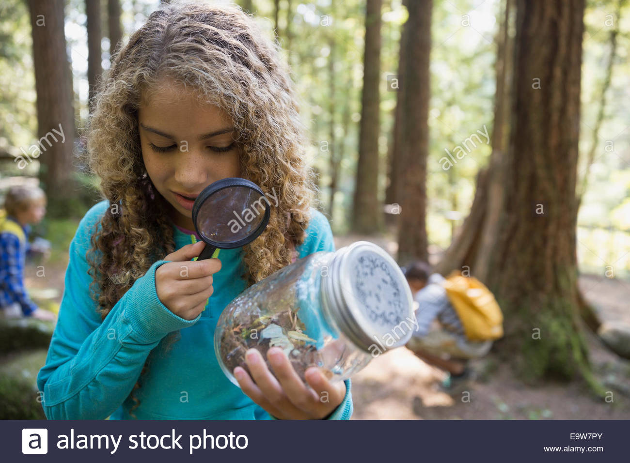 Girl with magnifying glass examining plants in jar - Stock Image