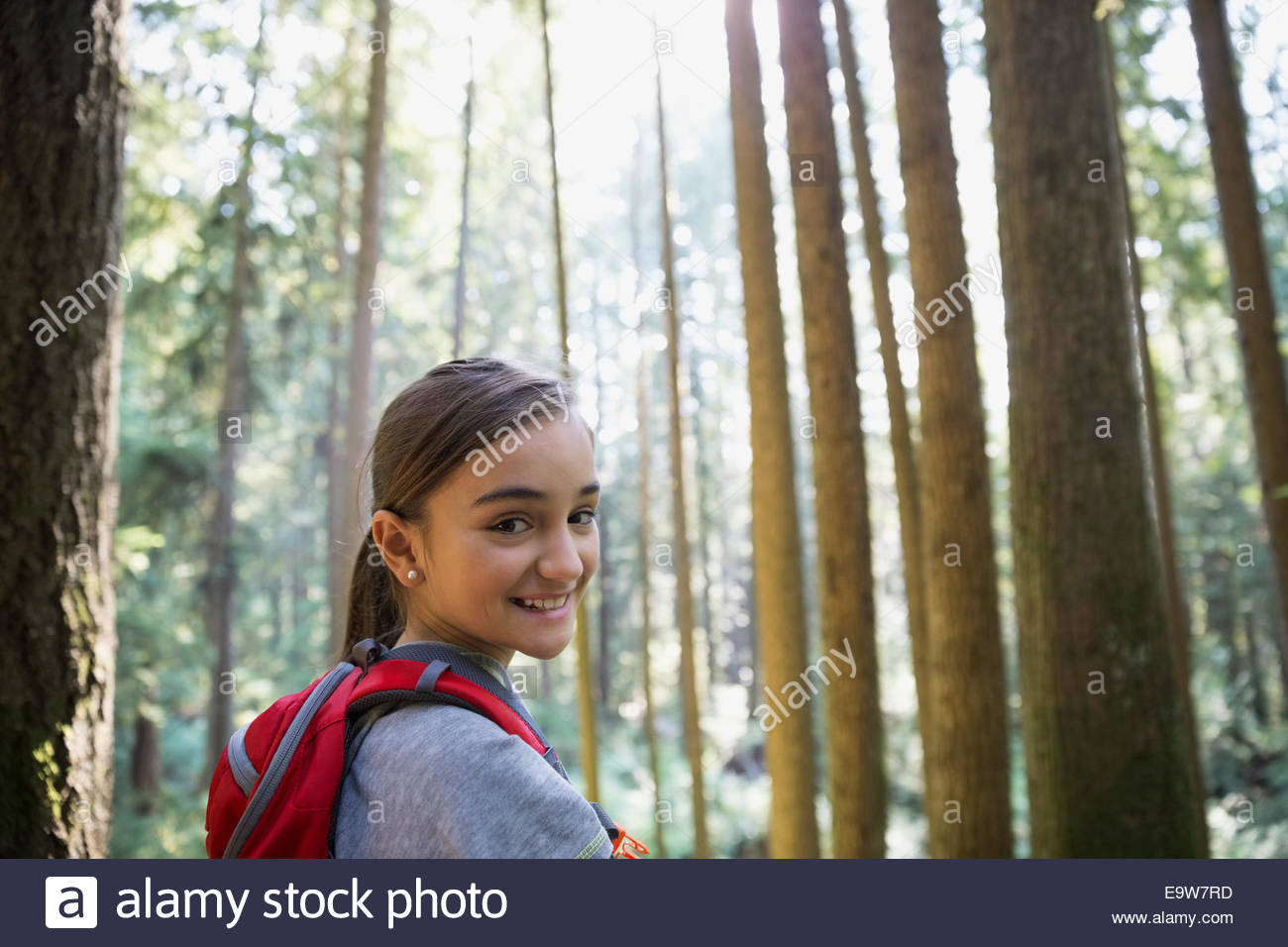 Portrait of smiling girl in woods - Stock Image