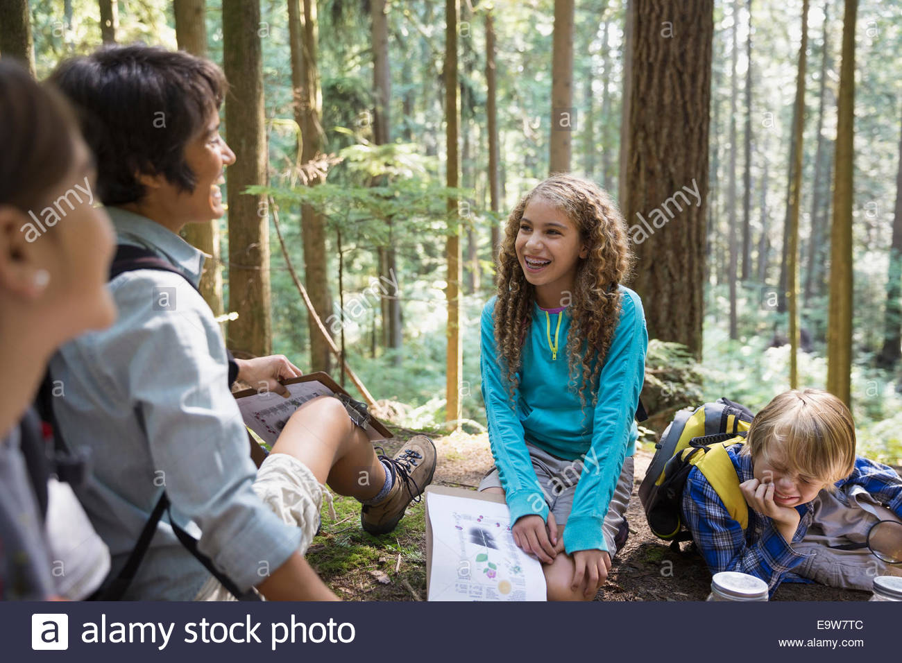 Teacher and children laughing in woods - Stock Image
