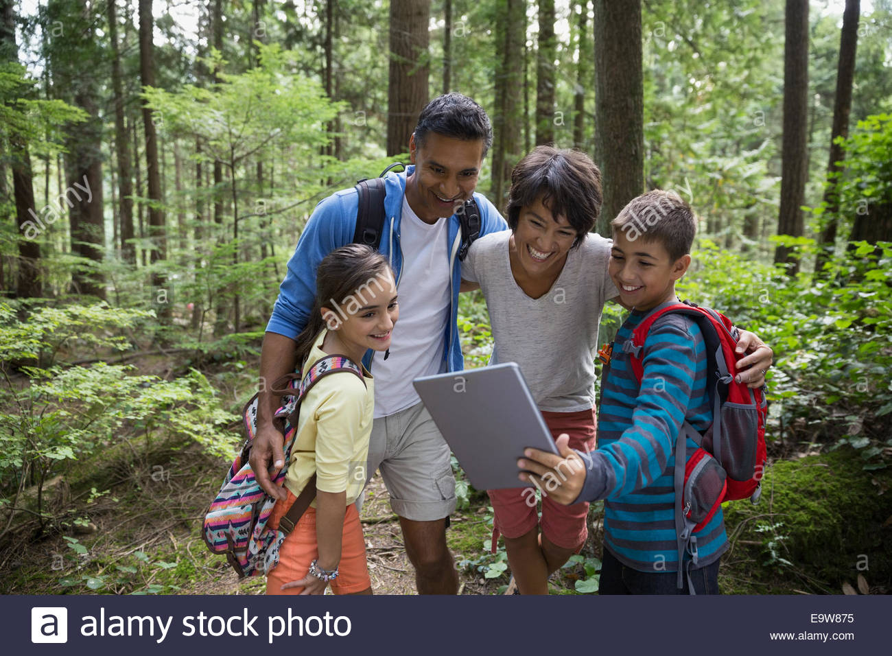 Family taking selfie with digital tablet in woods - Stock Image