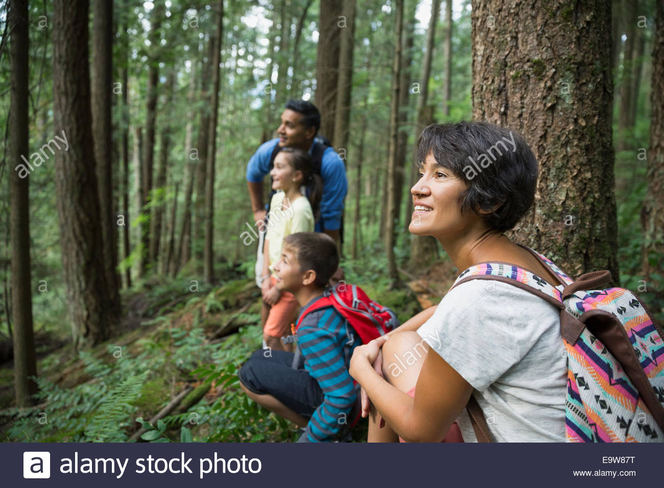 Family smiling in woods - Stock Image