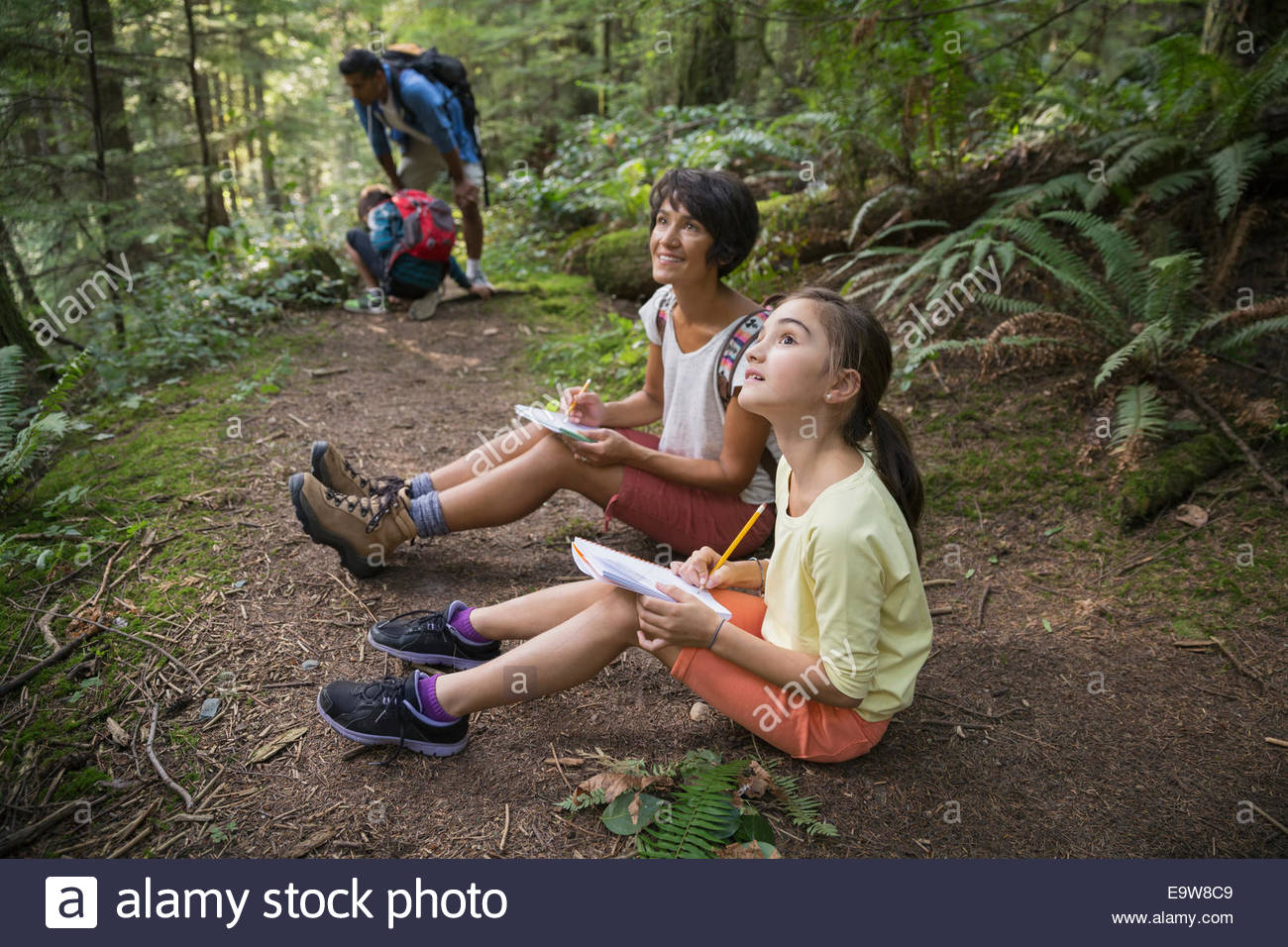 Mother and daughter with notebooks in woods - Stock Image