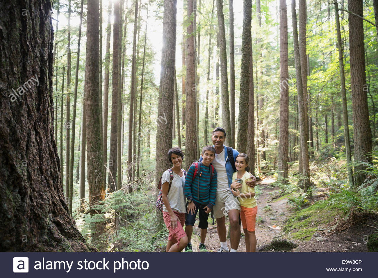 Portrait of smiling family hugging in woods - Stock Image