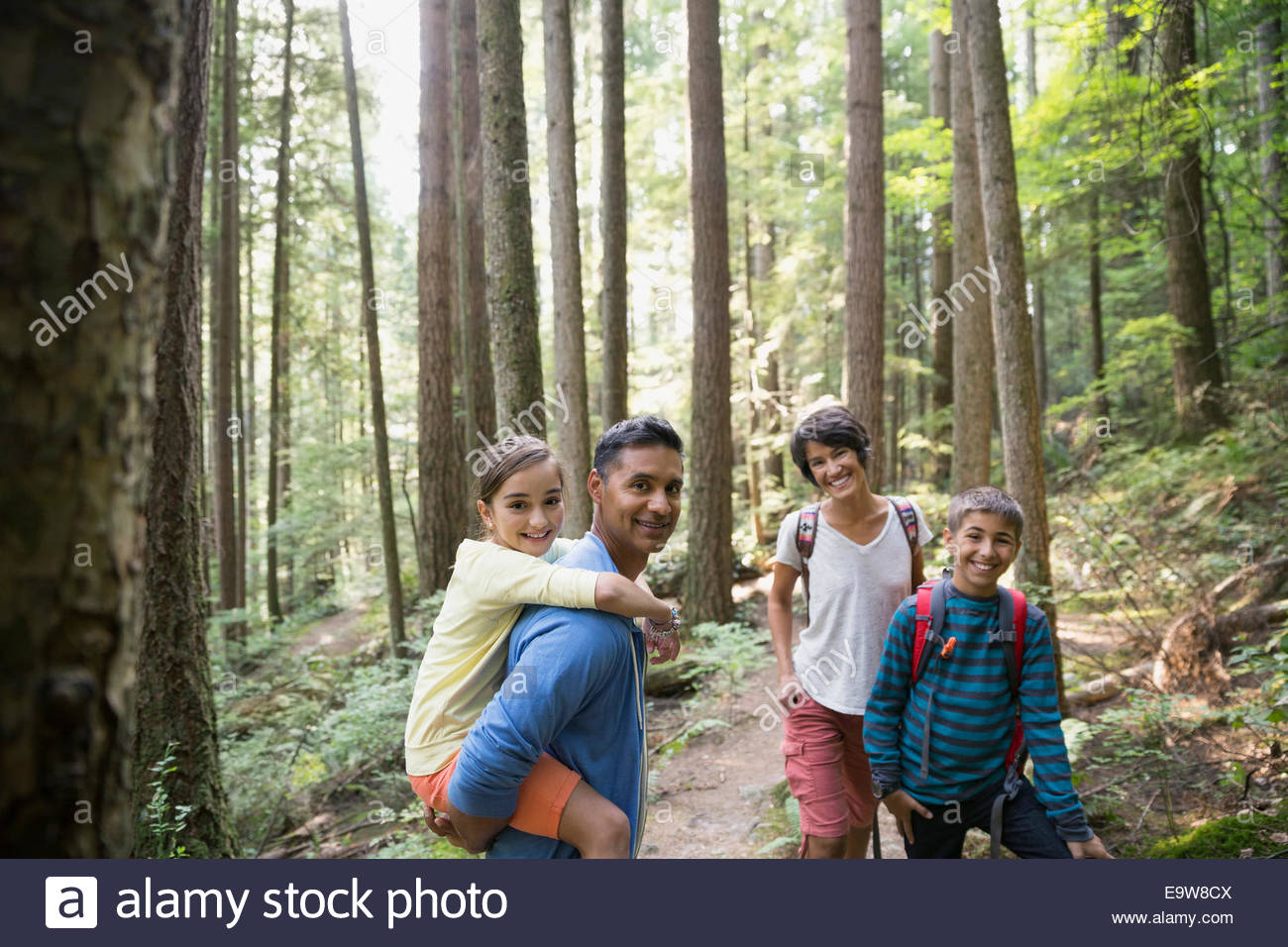 Portrait of smiling family on trail in woods - Stock Image