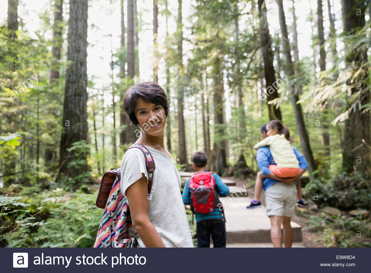Portrait of smiling woman with family in woods Stock Photo