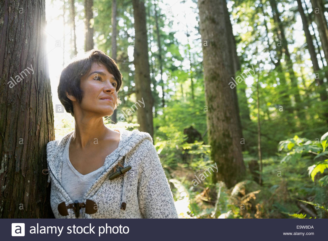 Serene woman leaning against tree in woods - Stock Image