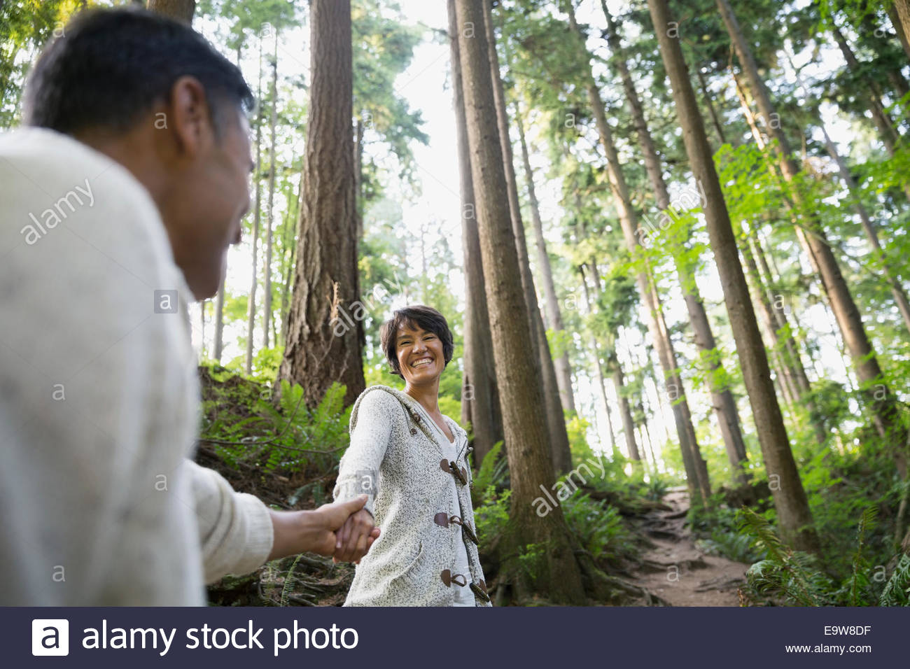 Couple holding hands on trail in woods - Stock Image