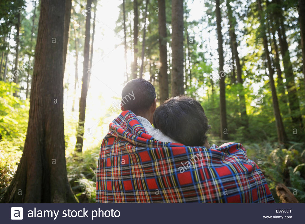 Couple wrapped in blanket in woods - Stock Image