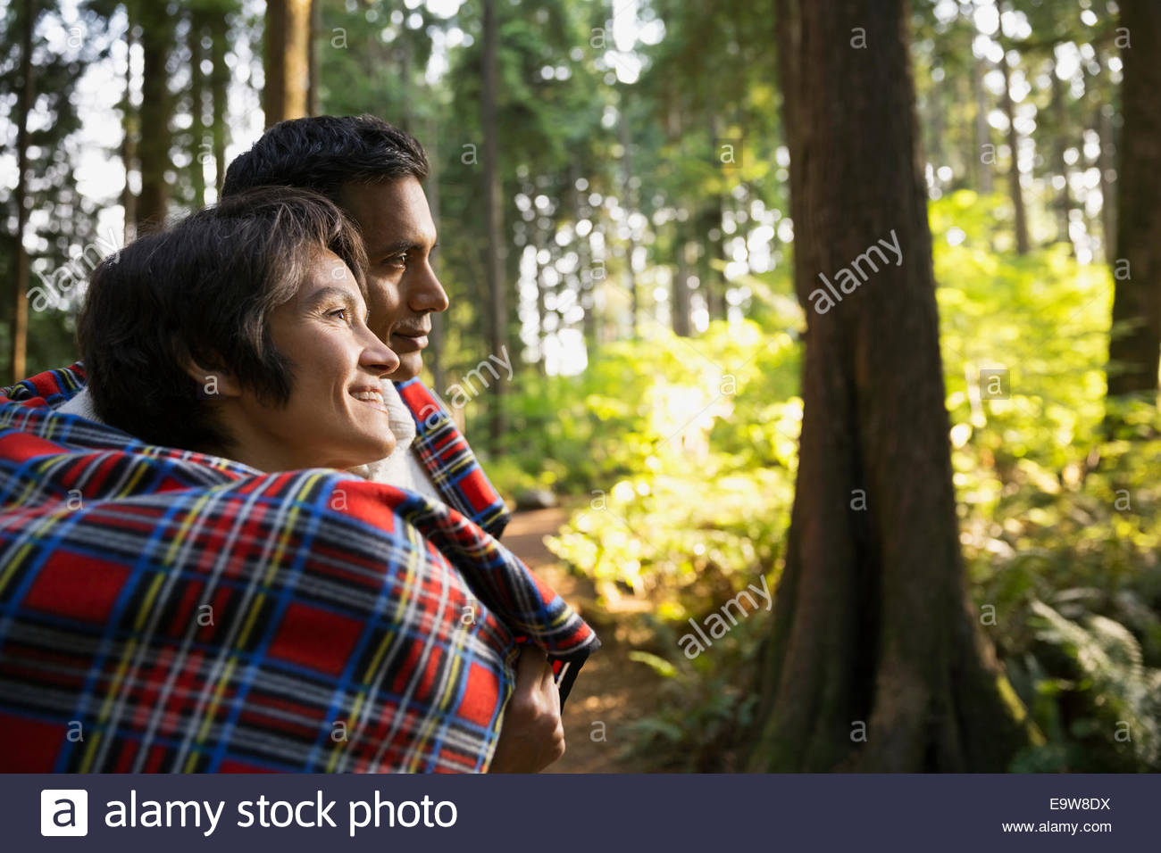Couple wrapped in blanket in woods Stock Photo
