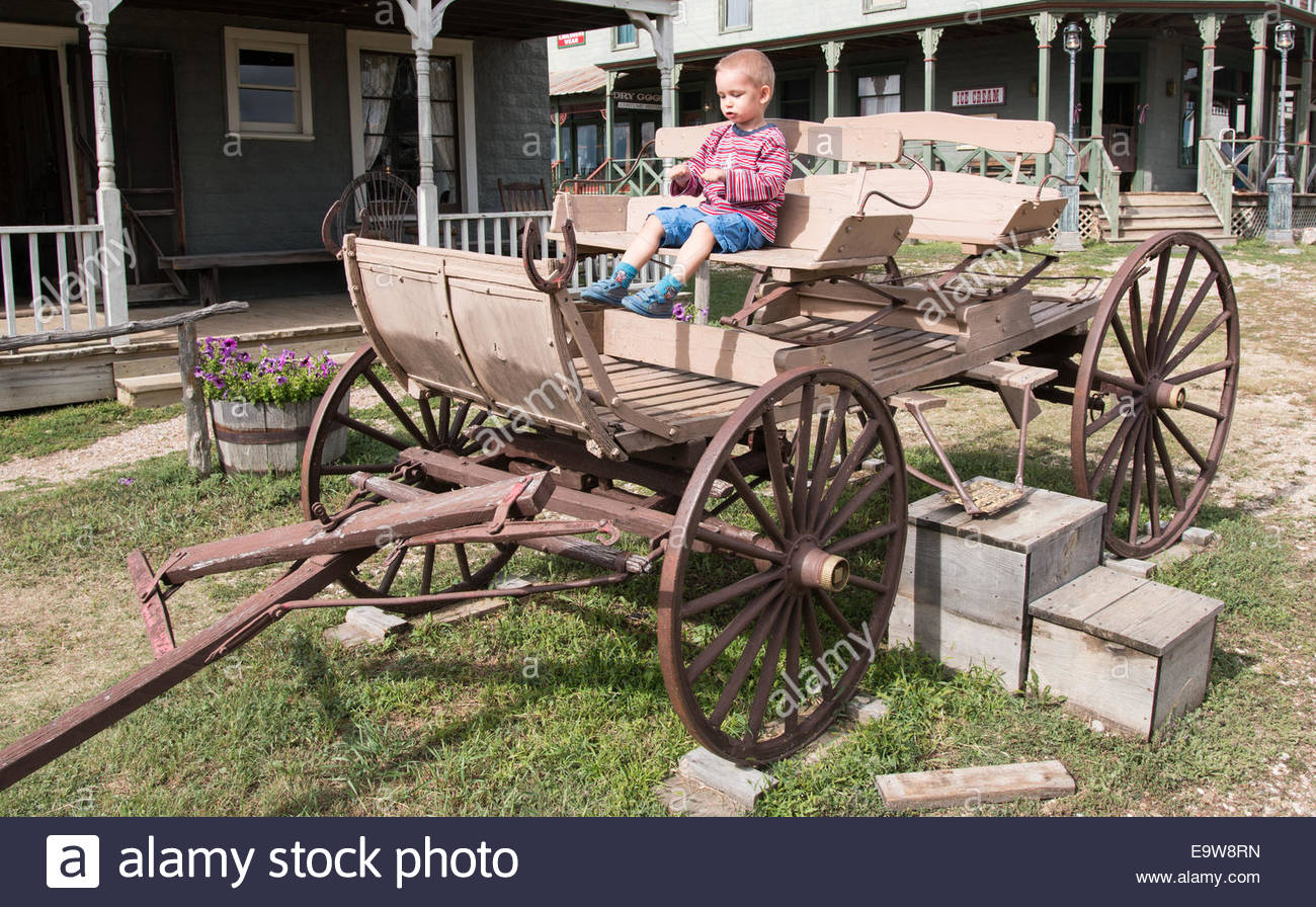 Little boy imagines that he runs a coach - Stock Image