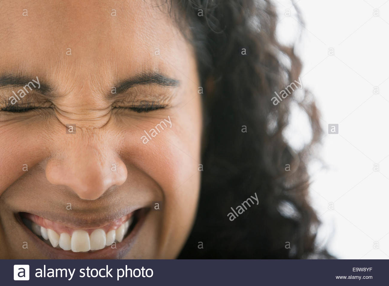 Close up portrait of smiling woman squinting - Stock Image
