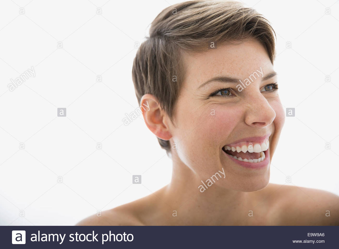 Close up of laughing blonde woman looking away - Stock Image