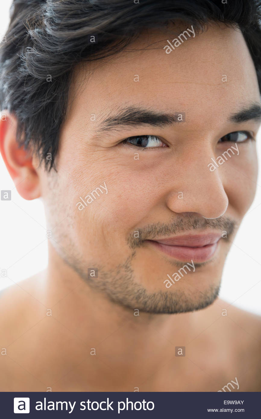 Close up portrait of mischievous bare chested man - Stock Image