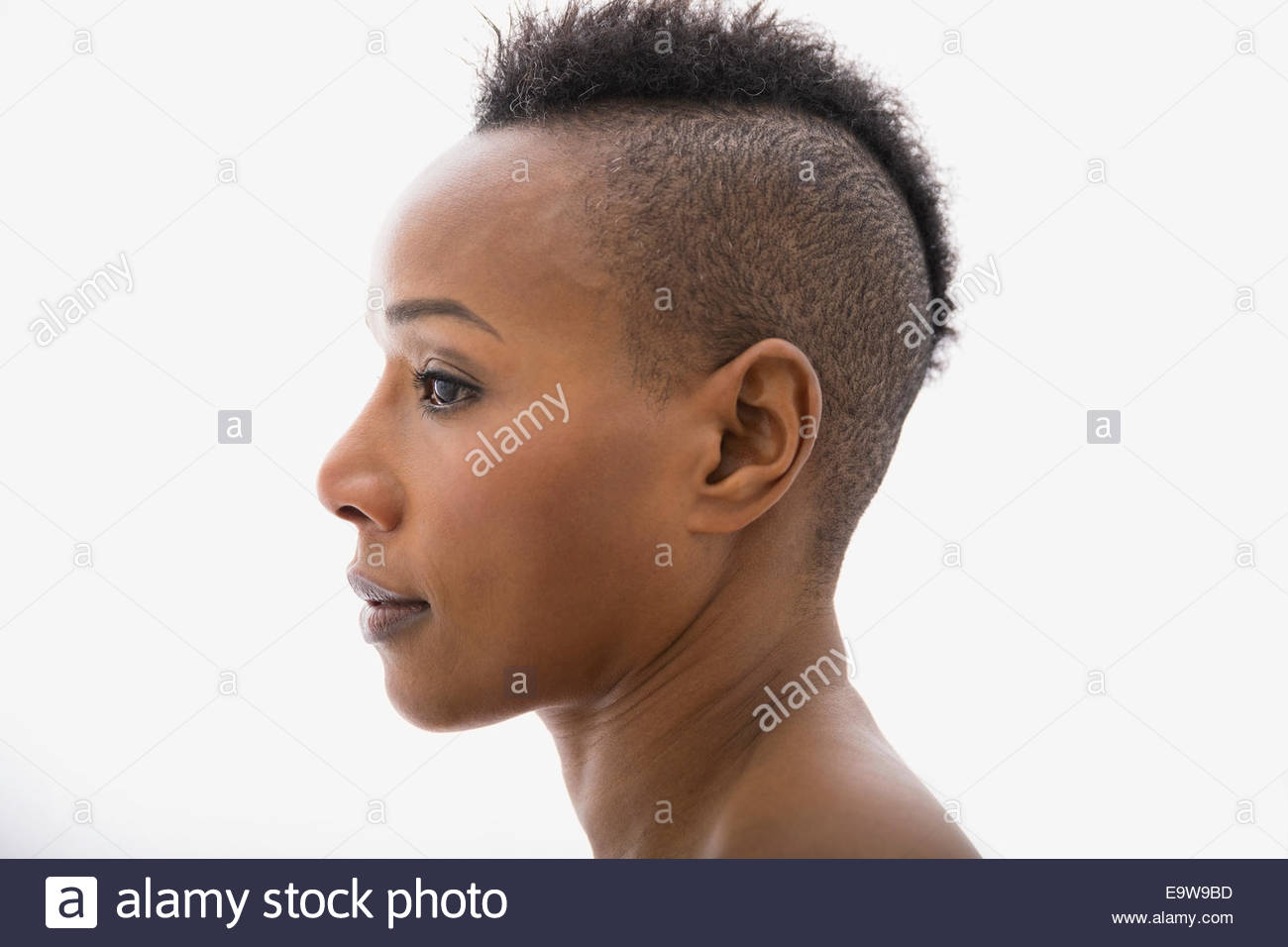 Close up profile of serious woman with mohawk Stock Photo