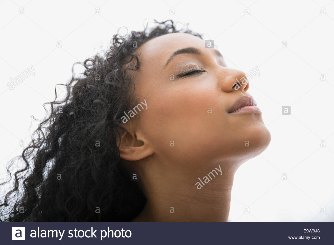 Serene woman with head back and eyes closed - Stock Image