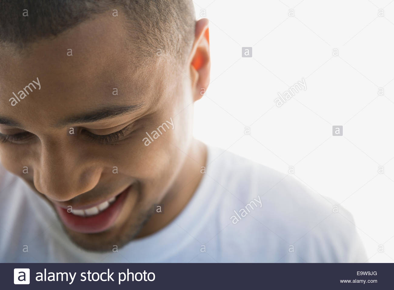 Close up portrait of smiling man looking down - Stock Image
